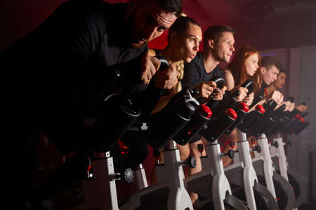 women and men on cycling machine working out in modern gym looking forward, side view on people during training Archivio Fotografico