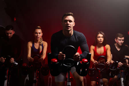 fitness people in a row exercising with bicycles in a gym. sport, lifestyle and healthcare concept