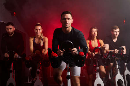 athlete people workout ride a bike in gym, with the intention of healthcare. caucasian men and women ycling to make body healthy with tight muscles and reduce the weight. male in the center