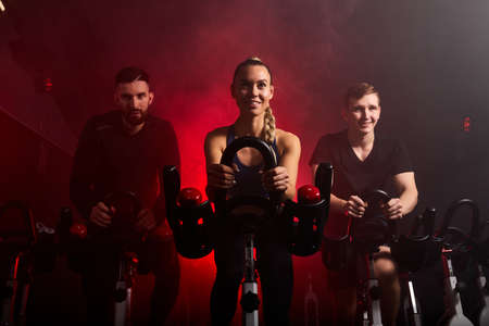fit people riding exercise bikes in gym, enjoying workout time, in smoky red neon space