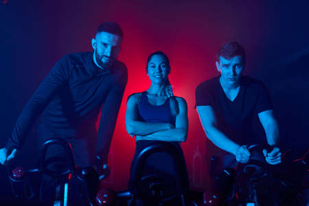 sportive people standing behind the bike in gym and looking at camera posing, in tracksuits Archivio Fotografico
