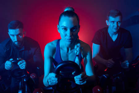 people working out on the exercise bike at the gym, intense cardio workout. men and women in sportive outfit training together, in blue neon lighted smoky space