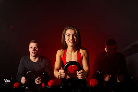 youth in sportswear, workout ride a bike in gym, with the intention of healthcare. caucasian men and women ycling to make body healthy with tight muscles and reduce the weight
