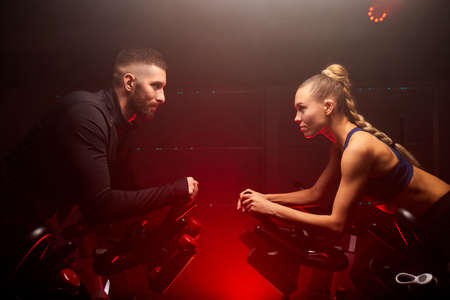 male and female sport people hold competition on bike in gym isolated on red neon lighted smoky space, oppsite of each other