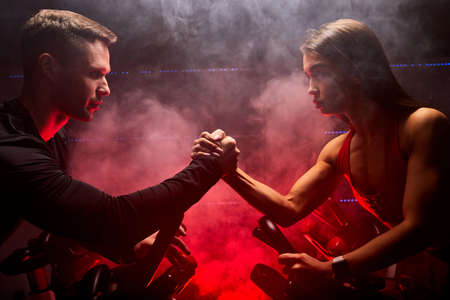 fit woman and man training on smart stationary bike indoors, sport competition in red smoky space. arm wrestling