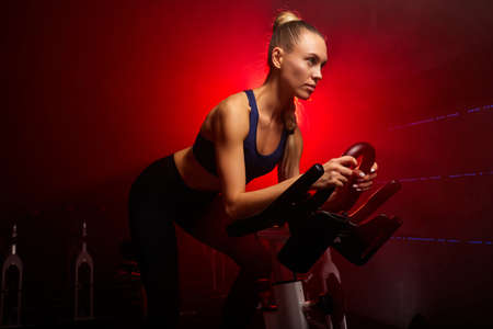 blond woman on bicycle working out at gym in smoky space, concentrated on workout Archivio Fotografico