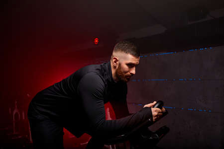 sportsman is exercising in class in fitness center, in red neon lighted smoky space, in black sportive outfit, has intensive training