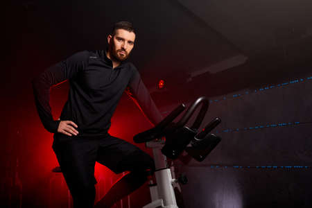 male sitting on bike in gym posing at camera, workout ride a bike in gym, with the intention of healthcare. red neon smoky space in the background