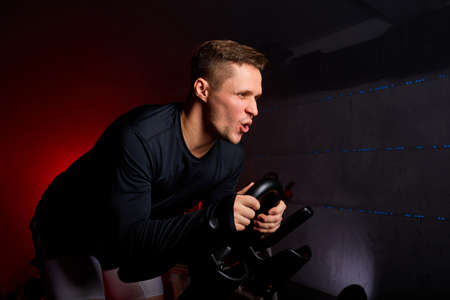 sportsman diligently riding an exercise bike in gym, the guy is exercising on a stationary bike