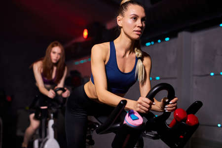 fit woman at the gym exercising on a stationary bike in gym. cardio exercises on bicycle, wearing sportive outfit, concentrated on workout