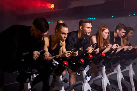 people taking weight loss with machine aerobic for slim body, sitting on bike, intensive cardio workout at fitness gym Archivio Fotografico