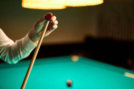 cropped male preparing billiards cue for game, close-up photo of hands. playing snooker game