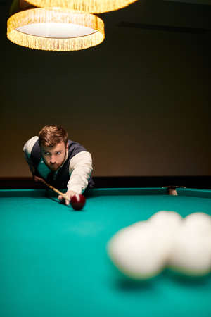 man leaning over the table while playing snooker, he is concentrated on game, having leisure time