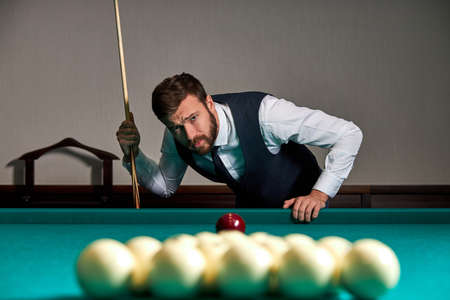 man playing billiard or snooker with concentration and serious face looking at balls on table, sport game concept