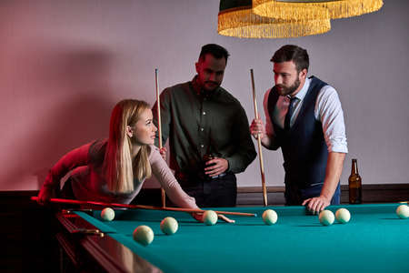 woman with two male friends are playing billiards in bar after work, have rest and leaisure time, preparing aiming to shoot pool balls