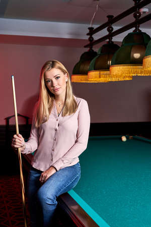 blond female came to spend pleasant time playing snooker, she is posing at camera, sitting on pool, billiards table Archivio Fotografico