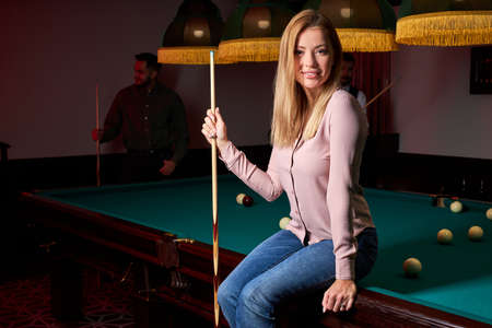 pretty woman in the bar next to billiards table pool, people playing snooker in the background. portrait