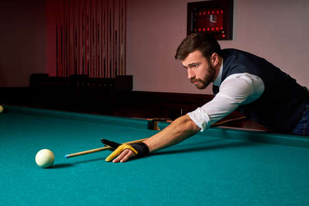male billiard player finding best solution and right angle at billard or snooker pool sport game, professional billiard player is concentrated Archivio Fotografico