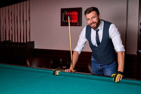 smiling male standing next to billiards table, looking at camera, posing, in formal wear. portrait