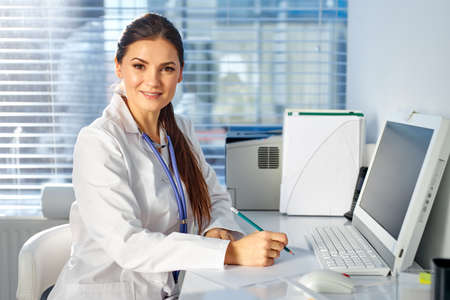 doctor woman sitting at desk making notes, at work place, in medical suit. professional therapist looking at camera and smiling Archivio Fotografico