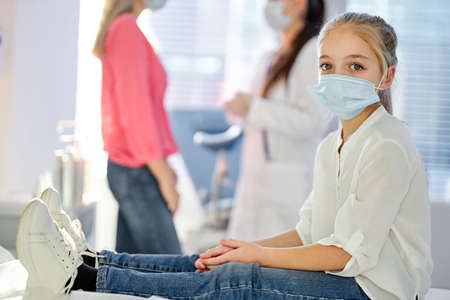child girl in medical mask looking at camera, sitting on bed in hospital or clinic while her parent mother talking with nurse in the background