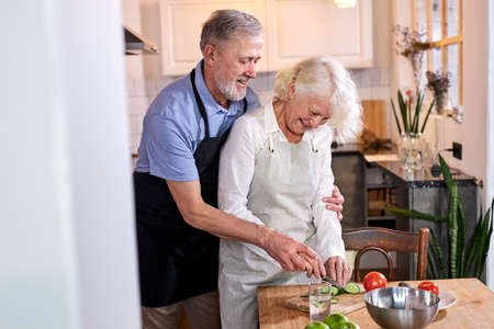 elderly couple carving vegetables together, handsomegray haired man help wife to cook Banque d'images