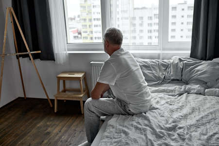 side view on upset man sitting alone on bed at home in dark room, morning alone.