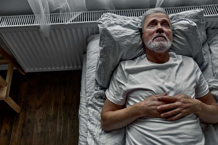 middle-aged man lying down in bed on pillow, having insomnia sleeping disorder. alone at home