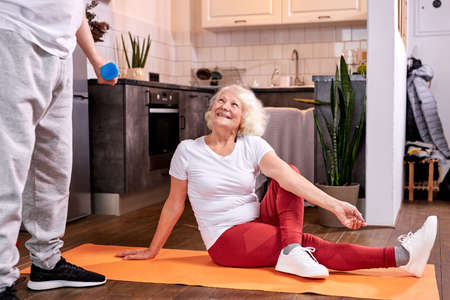 woman sits stretching on the floor while husband workout with dumbbells, she looks at him and smiles Standard-Bild