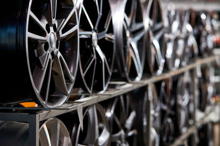 stand with alloy wheels in modern tire store, close up photo of auto wheels in auto service shop
