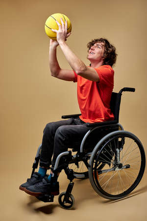 disabled man in wheelchair train with basketball ball, caucasian athlete exercising, despite disability. side view