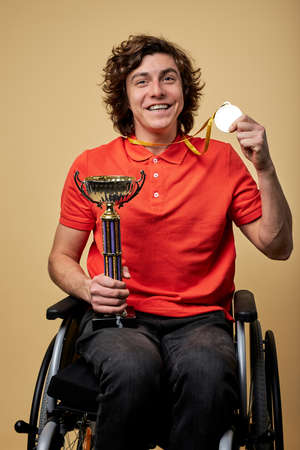 happy disabled sportsman in wheelchair holding champion goblet and gold medals isolated on beige background