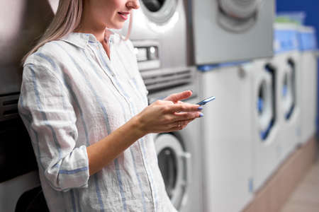 Laundry, smiling woman holding phone, washing clothes via app. Cropped young caucasian female is ready to wash clothes
