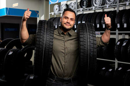 client guy stands with two tires by rack of tires, he made choice, buy the best ones in auto service shop, showing thumbs up at camera, happy. portrait