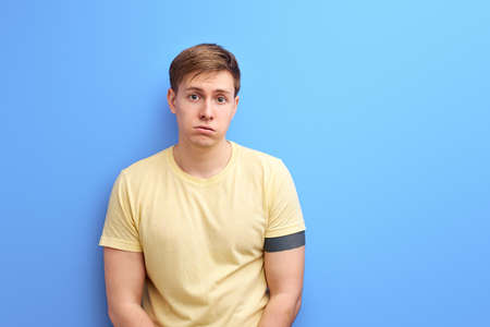 upset man standing and looking at camera with dissatisfied sadness face, indoor studio shot, isolated on blue background, portrait
