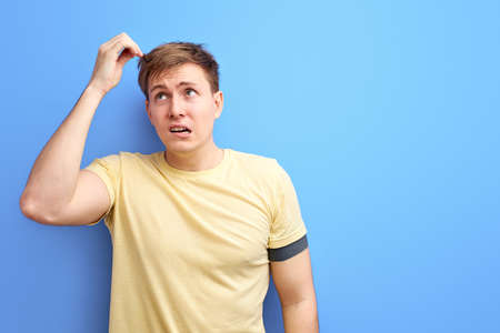 man looks away and thinks with a doubtful face, try to remember something, isolated on blue background. studio portrait of caucasian male in casual t-shir looking up