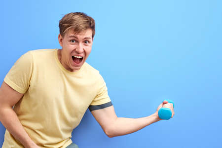 non-athletic male holding small dumbbell in hands, it is difficult for him to lift it, scream, stand with wide opened mouth, training, pumping arm muscles. isolated blue background