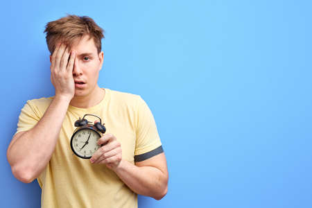man in t-shirt hold alarm clock in the morning, has no enough sleep, cant wake up. isolated on blue colour background studio portrait.