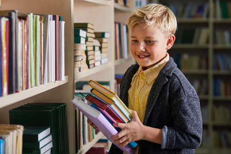 child boy holding books in hands in library, enjoy beind educated, preparing for school