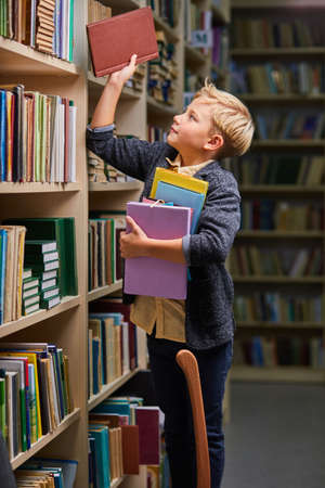 school boy taking books from shelves in library, with a stack of books in hands. child brain development, learn to read, cognitive skills concept Archivio Fotografico