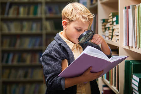 school little boy using magnifying glass for reading, get new information for brain in library