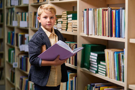 kid boy reading book between bookshelves in campus library, empty space. child is ready for school. education concept