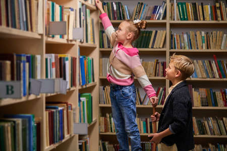 brother and sister choose books in library, having conversation, in library of school Archivio Fotografico