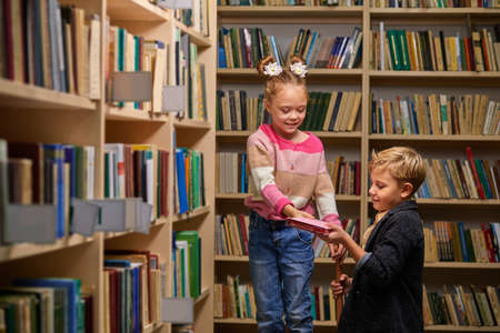 two school children help each other to get a book from shelf, stand talking, in library