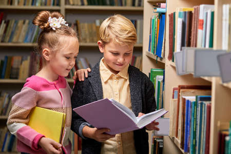 boy and girl reading book in school library, people lifestyles and friend Education and friendship concept. leisure time for children, group activity