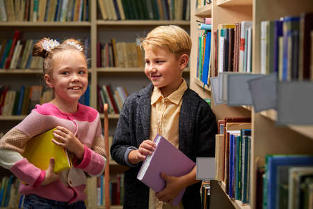 children have fun in the library, girl and boy talking and laughing, discussing school, stand between books shelves Archivio Fotografico