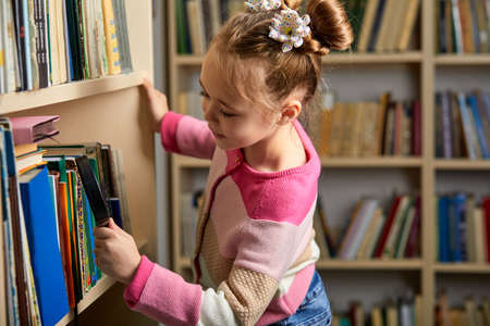 kid girl with ponytails choosing books in library after classes, enjoy being educated, get new information and knowledge