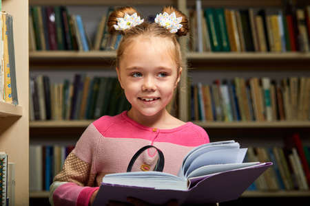 girl in casual wear in library after school, reading an encyclopedia,diligent child use magnifying glass Archivio Fotografico