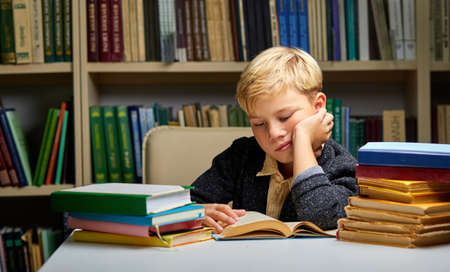 sleepy boy sitting at table with books in library. tired to study. Education, Knowledge, Bookstore, Lecture concept