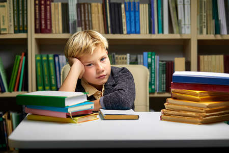 sleepy little boy tired of learning doing homework reading book, studying preparing for exam test, literature research, children education concept